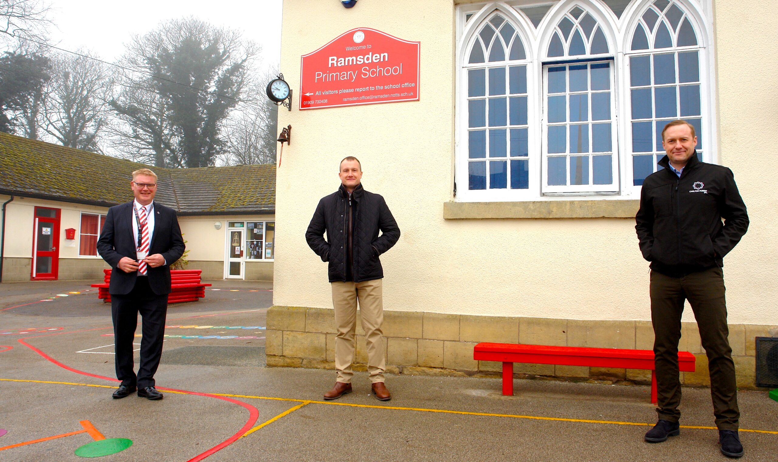 three men stood social distanced outside of primary school
